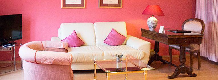 Sitzecke im Einzelzimmer Deluxe mit Sofa, Stuhl und Tisch