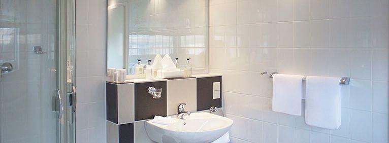 Einblick ins Bad des Einzelzimmer Deluxe mit Waschbecken und Spiegel