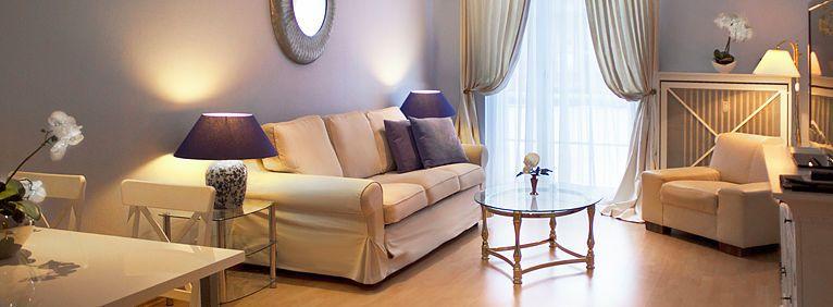 Übersicht des Wohnbereichs in der Suite mit Sofa, Sessel und Esstisch